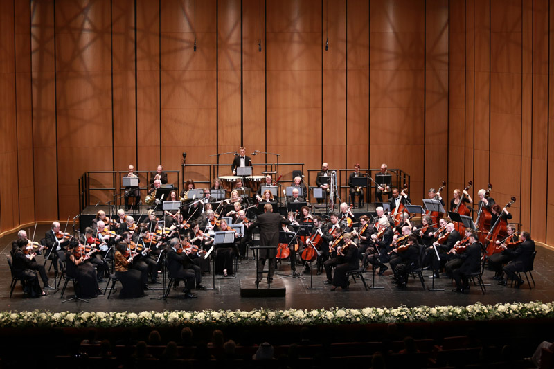 Orchestra playing on a stage with a wood background