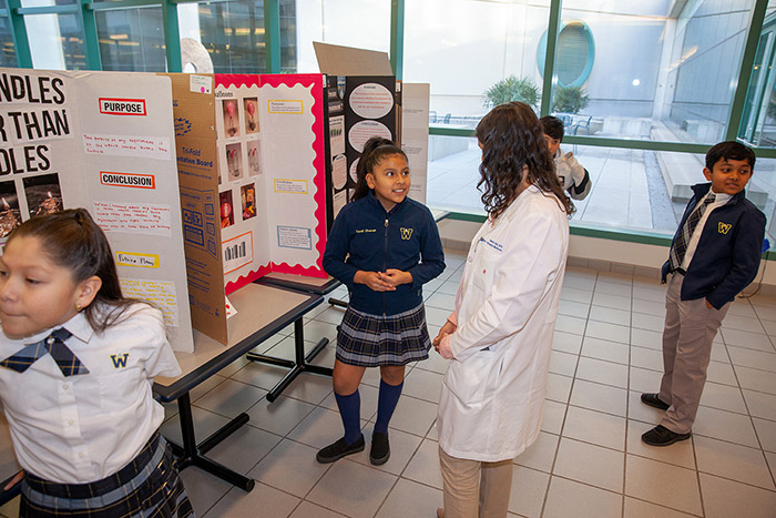 Girl talking to woman in white lab coat about her poster