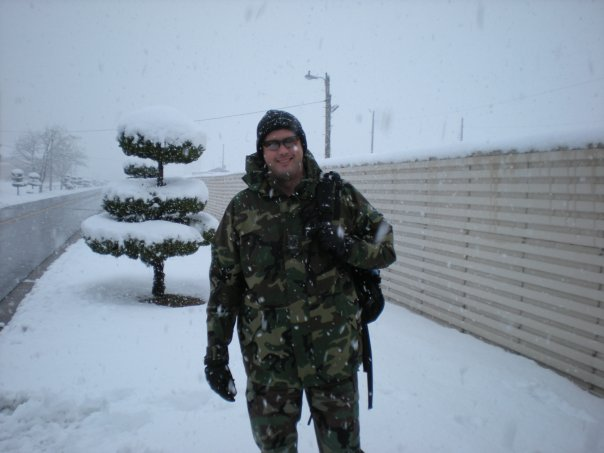 Man outdoors in the snow wearing military camo