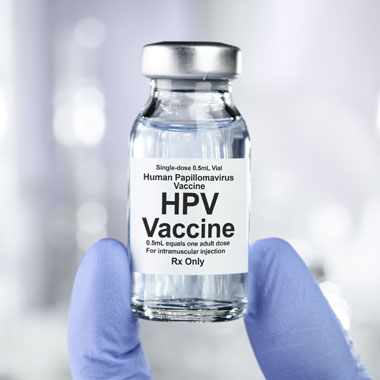 Someone holding a bottle of HPV vaccine with two gloved fingers