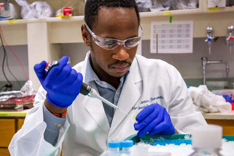 Postdoctoral scholar fills a pipette in the research lab