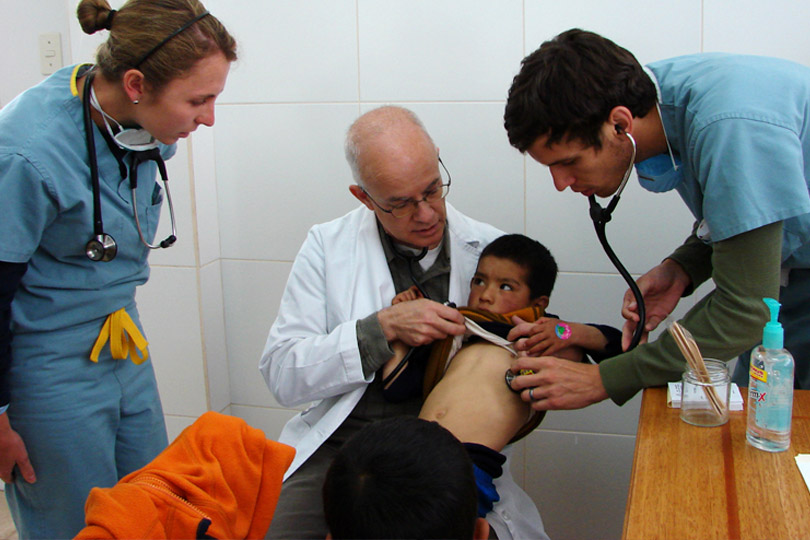 Two medical students check a young boy's heart beat in a clinic