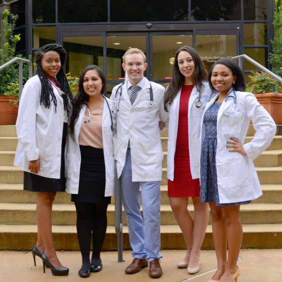 Four female medical students and a male medical student stand in front of a building on the UT Southwestern campus