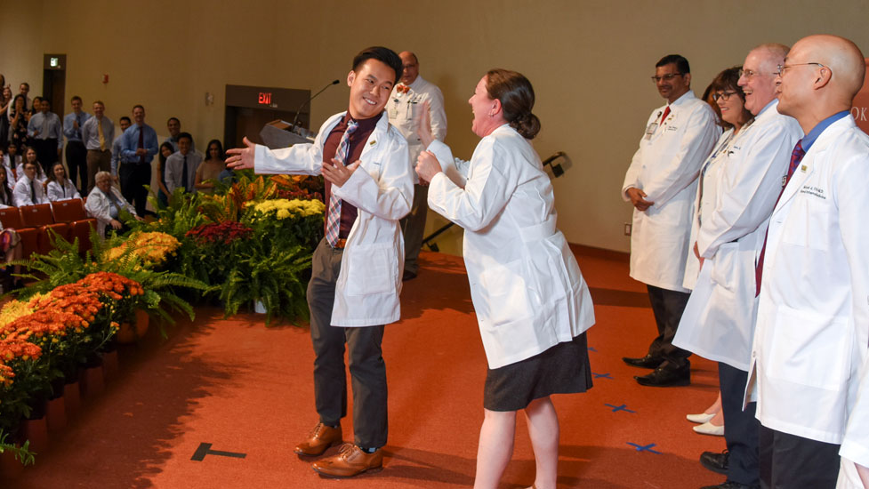 A student and faculty laugh during the White Coat Ceremony