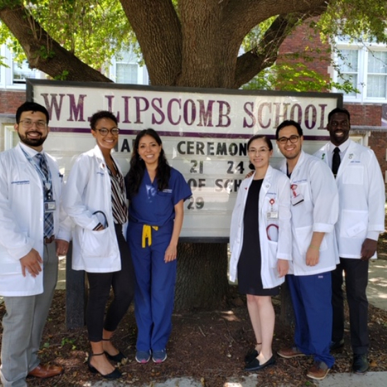 Three female and three male medical students stand in front of an elementary school sign