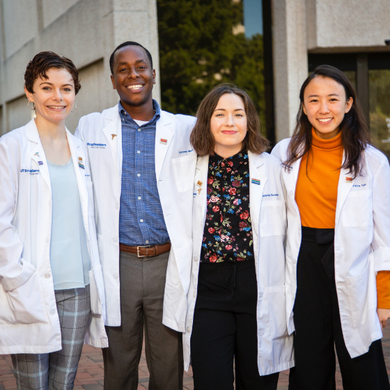 One male and three female medical students in their white coats