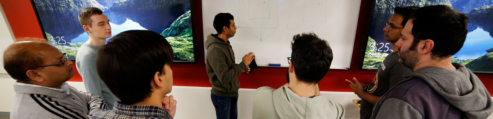 Male students gather around as a classmate develops an idea on a whiteboard