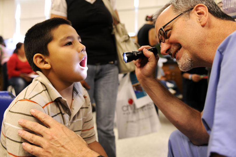A medical student looks a child's throat during a clinic at United to Serve