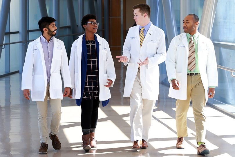 Diverse medical student walking across a skybridge