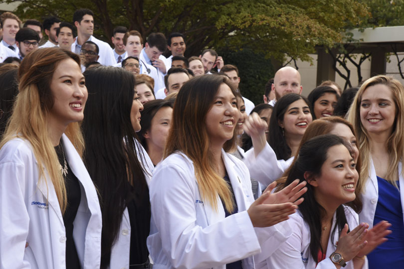 Students in white coats stand in a group outside