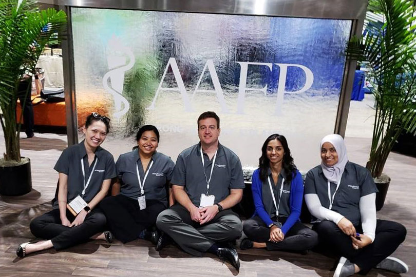 A man and four women sit in front of a frosted glass AAFP sign