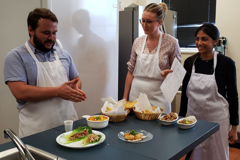 A man and two women prepare lettuce wraps and other healthy food in a culinary medicine class