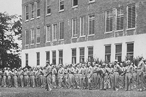 Soldiers lined in front of large brick building