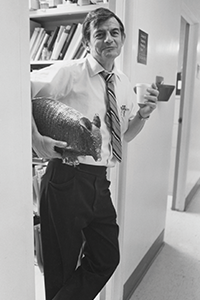 George Curry in office doorway, holding a styrofoam cup in one hand with a stuffed armadillo under his arm