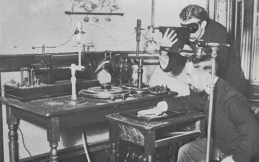 Historic photo of one man holding his hand on an X-ray plate while another operates machinery