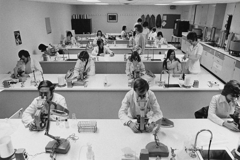 Students in the classroom in 1968 looking into microscopes