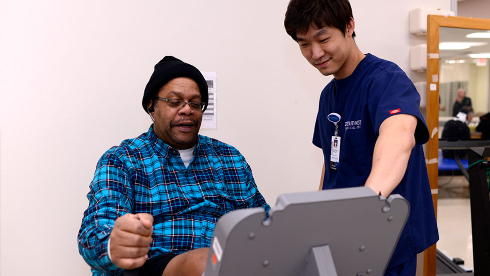 Student working with a patient on an exercise machine
