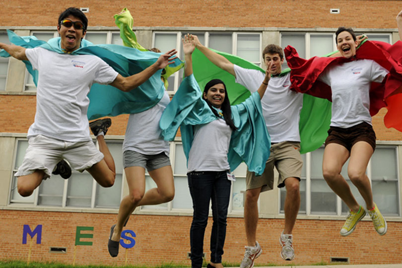 Five students leap into the air while wearing capes at United to Serve.