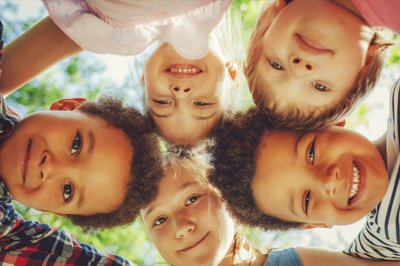 Five young children put their heads together to form a circle while looking down at the camera