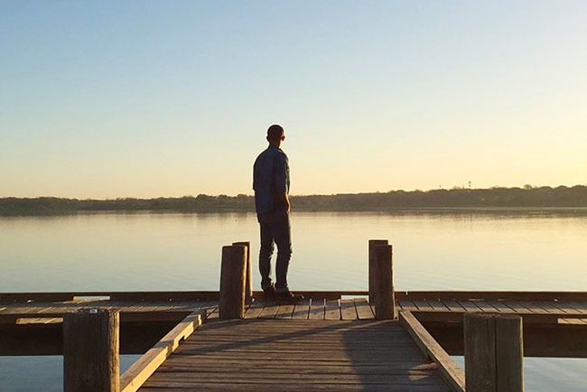 Person on boat dock overlooking calm White Rock Lake