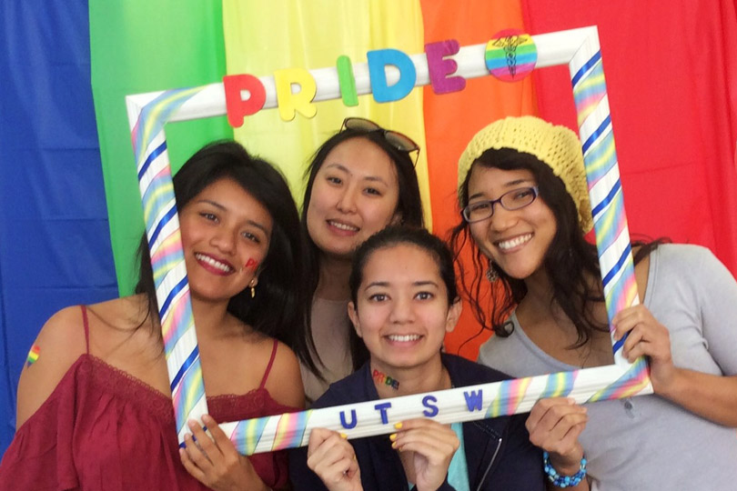 Four women holding a UTSW Pride picture frame
