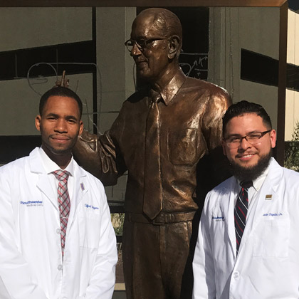 Two male students stand by the statue of Dr. Donald Seldin after their white coat ceremony