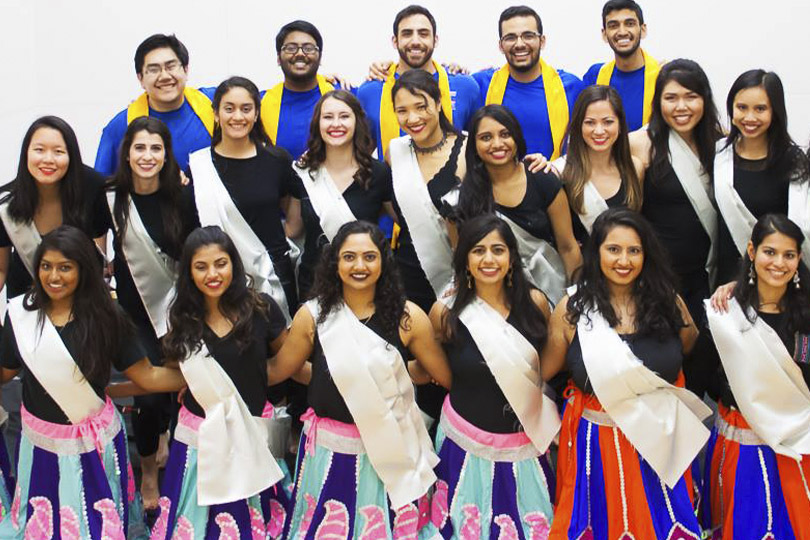 Women dancers wear black tops with pink and blue skirts and white sashes and men wear blue shirts with yellow sashes.