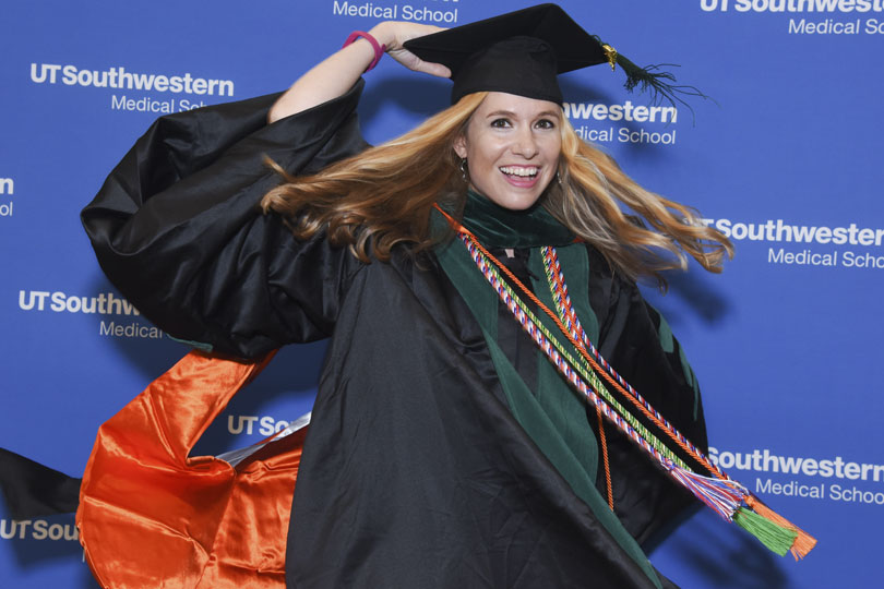 A student wearing her cap and gown spins quickly to the side