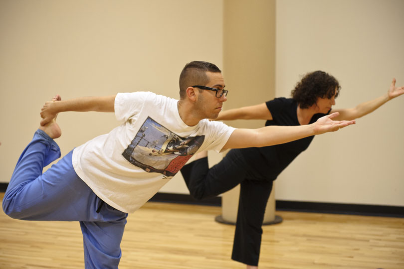 A man and a woman stand on one leg and stretch in the dancer pose during a yoga class m
