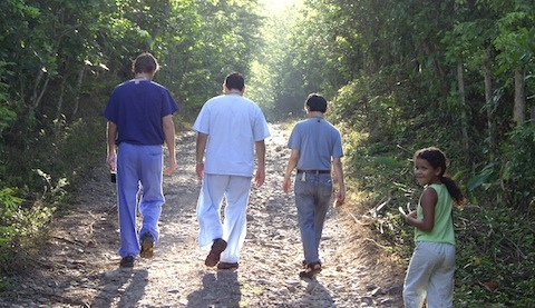 Tommy Heyne '12 walking down a path with people in Honduras