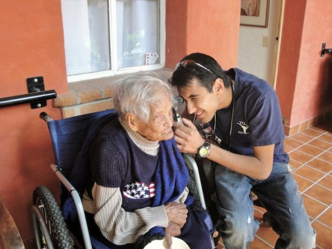 UT Southwestern student performing an ear exam on an elderly man in Mexico.