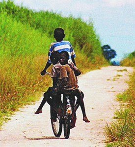Three children riding a bicycle along a dirt road in Zambia.