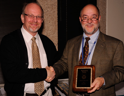 Dr. Greg Fitz, Dean of UT Southwestern Medical School presents award to Dennis Burns, M.D., Professor of Pathology.