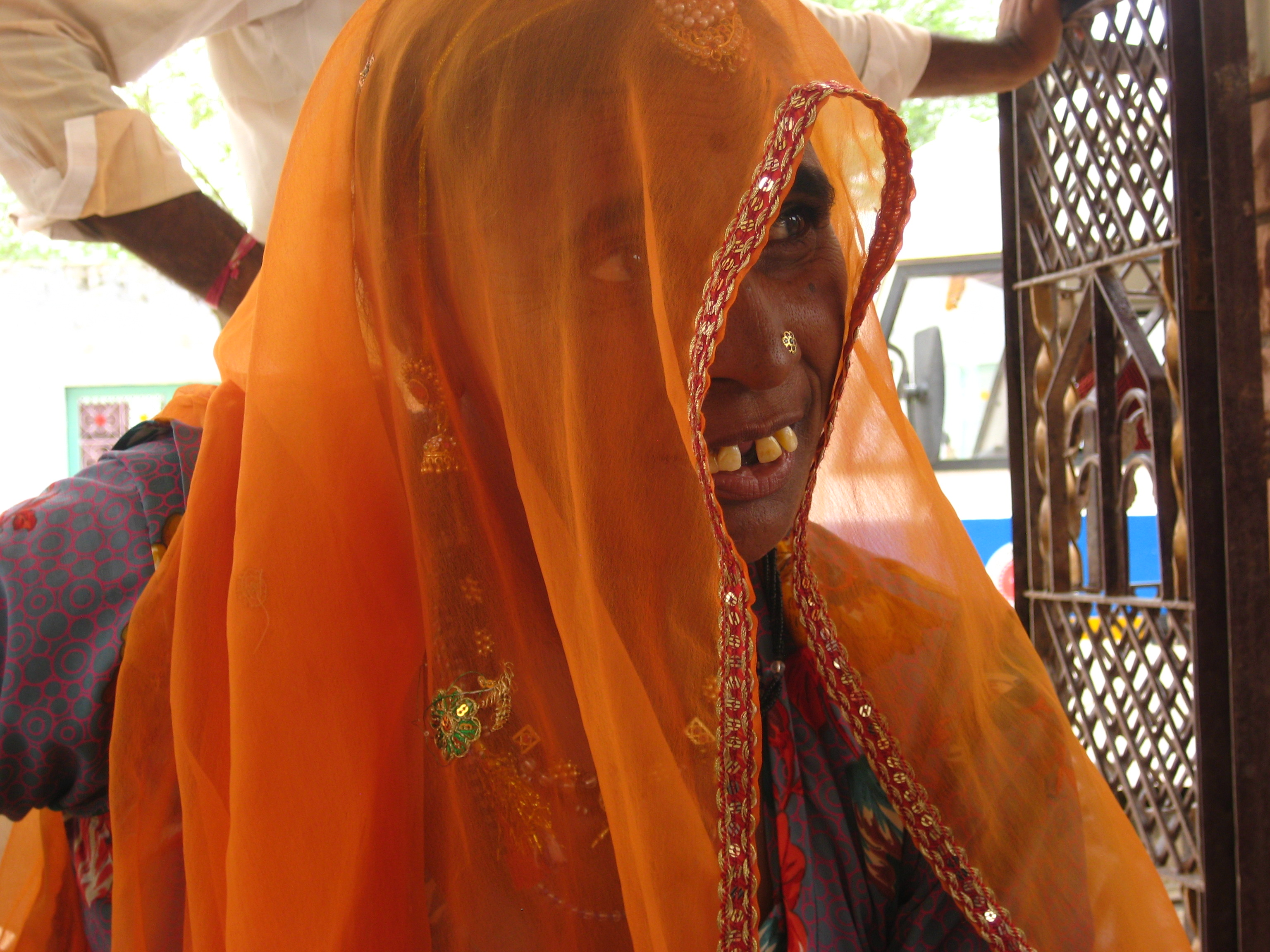 Indian woman with orange scarf over her head