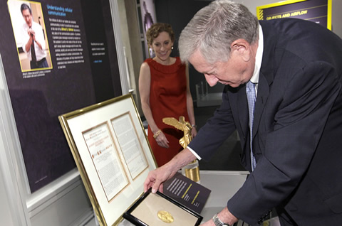 Dr. Alfred Gilman places his donated 1994 Nobel Prize medal in Physiology or Medicine for display at the Perot Museum as Nicole Small, the museum's Eugene McDermott CEO, looks on.