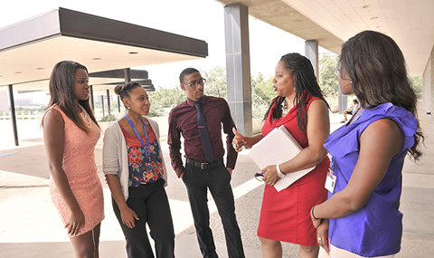 Kimel Hodges (second from right), Assistant Vice President for Diversity & Inclusion and Equal Opportunity, talks with summer interns (from left) Jabria Rahsaan, Taliah Royal, Sean Reed, and Karolyn Palmer (right) outside the Paul M. Bass Administrative and Clinical Center.