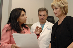 Drs. Roshni Rao (left), a surgical oncologist, and Michael Ulissey, a radiologist, visit with patient Joan Hollers to discuss her recovery after undergoing surgery to remove a breast tumor.