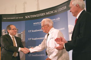 William P. Clements Jr. (center), wearing a new white coat, is congratulated by Dr. Daniel K. Podolsky and William T. Solomon at Friday's ceremony announcing a $100 million gift from the former Texas governor for UT Southwestern.