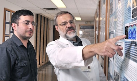 Drs. Rami Hallac and Ralph Mason view a poster.