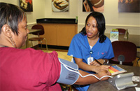 UT Southwestern employee checks a patient's blood pressure