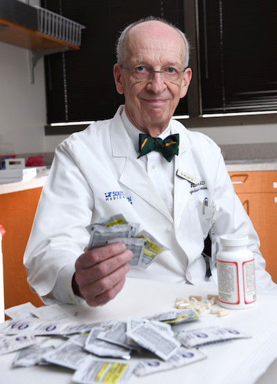 Dr. Lee holding packets of acetaminophen-containing products