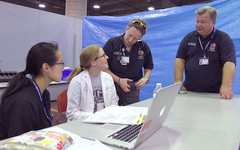 "Dr. Raymond Swienton, right, meets with other members of the medical response team at the Mega-Shelter Medical Clinic at Kay Baily Hutchison Convention Center."" width="