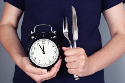 Person holding a clock, a fork and a knife