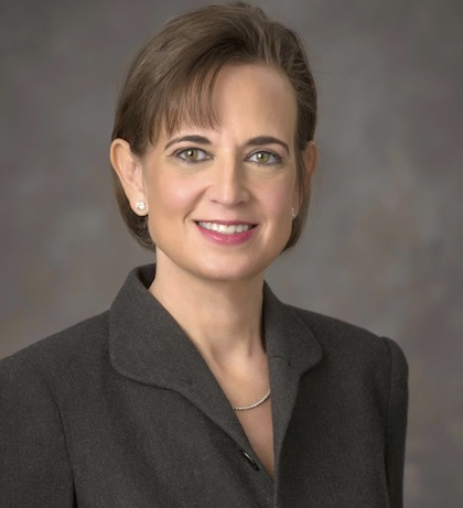 A woman with brown hair and black blazer